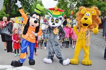 Chodzące postacie bajkowe Goofy, Król Julian, Lew Alex na paradzie z okazj Dni Miasta